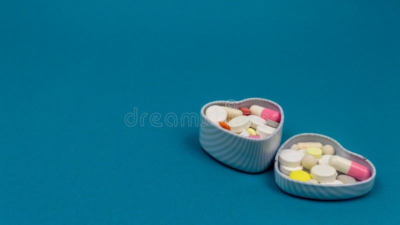 铁片剂的心脏箱子在蓝色背景 圆,卵形,白色,红色 r 库存照片