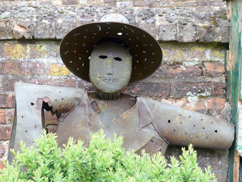 铁稻草人身分对在切尼斯庄园住宅的庭院墙壁 库存图片