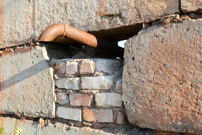 铁管子的末端黏附在一个水泥砖墙外面 库存照片