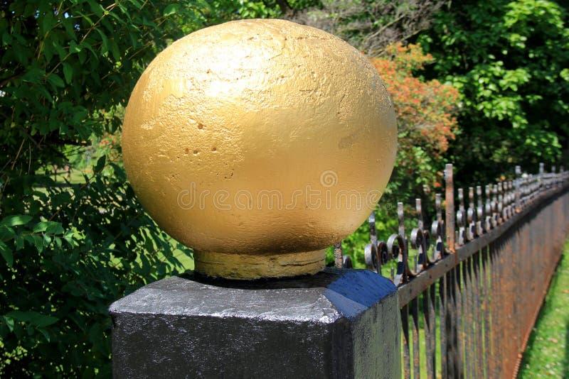 黑锻铁篱芭的长度有大金子的上色了在一个末端的球 免版税库存图片