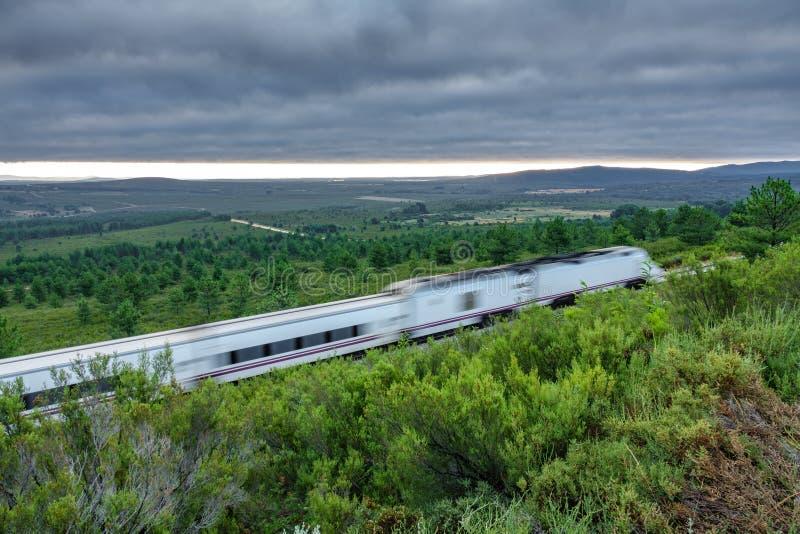 铁路和被弄脏的快车在国家,多云天空 图库摄影