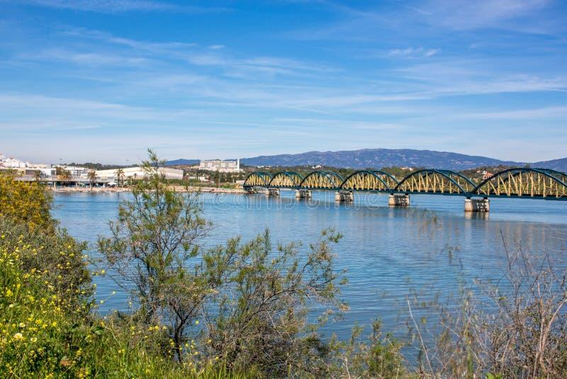 铁路桥的看法在河Arade和城市波尔蒂芒,葡萄牙,欧洲的 免版税库存照片