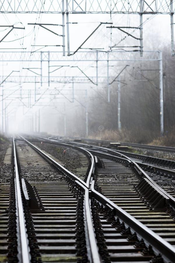 铁路轨道交叉路在雾的 免版税库存图片