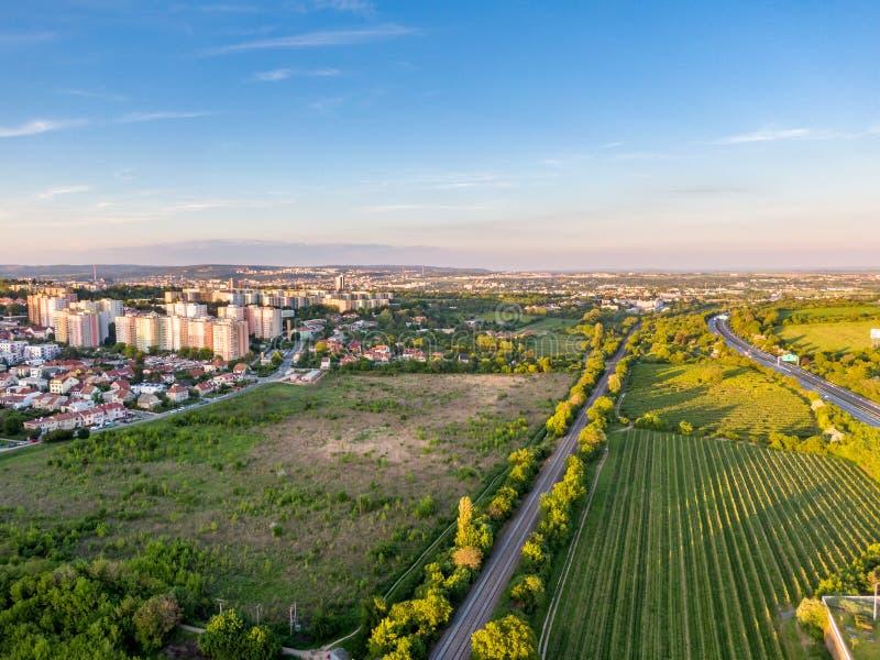 铁路鸟瞰图在日落期间的 城市全景在背景中 树、草和灌木在前景 免版税库存图片