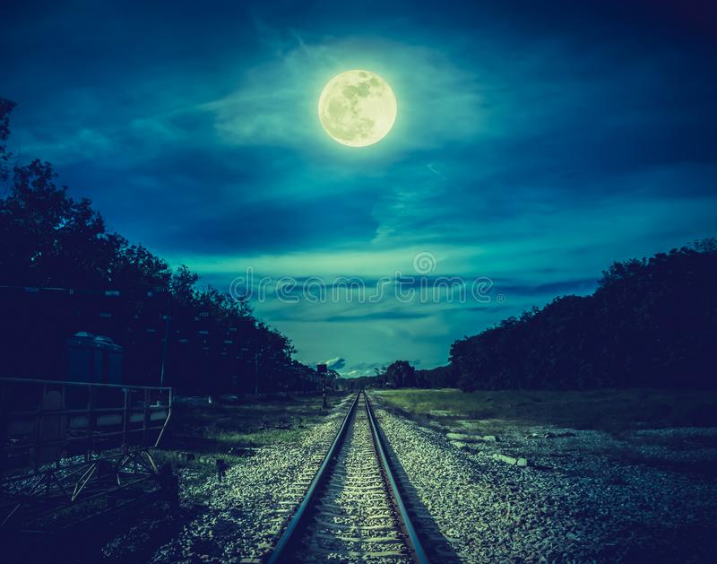 铁轨通过森林在晚上 美丽的天空和满月在树和铁路上剪影  平静自然 免版税库存图片