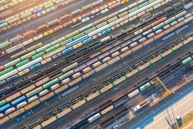 铁轨长的火车鸟瞰图,排序驻地的货物 有货物和原料的许多不同的火车 免版税库存图片