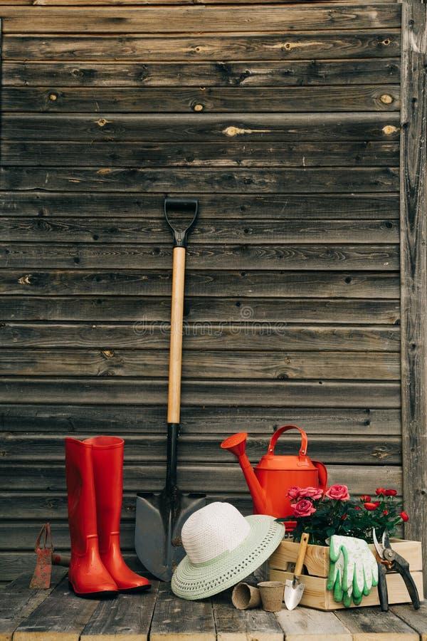 铁锹、喷壶、帽子,胶靴、箱花,手套和园艺工具 免版税图库摄影