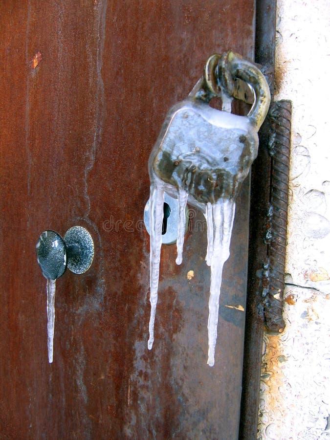 铁门特写镜头与老生锈的锁的结冰与冰柱 库存照片