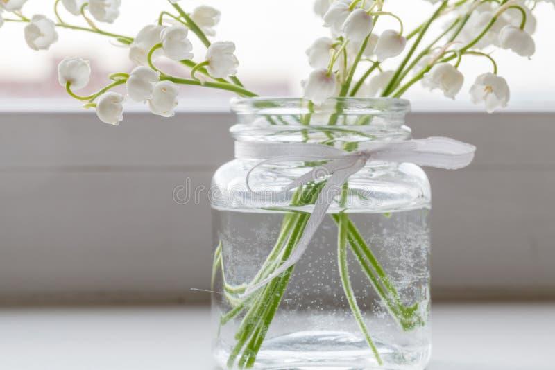 铃兰花束在w的一个简单的玻璃花瓶 库存照片