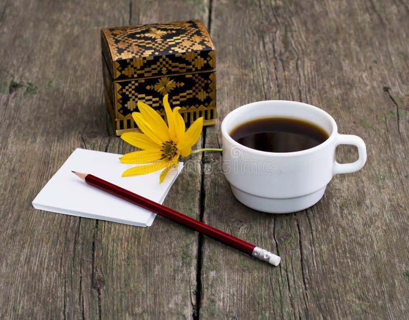 铅笔、咖啡和用一朵黄色花装饰的小箱 图库摄影