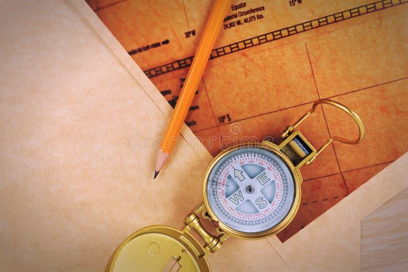 铅笔、指南针和葡萄酒在一张木桌上映射 免版税库存图片