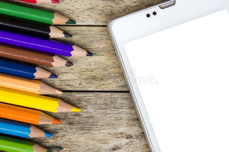铅笔上色和在木背景,顶视图的巧妙的电话 免版税库存图片