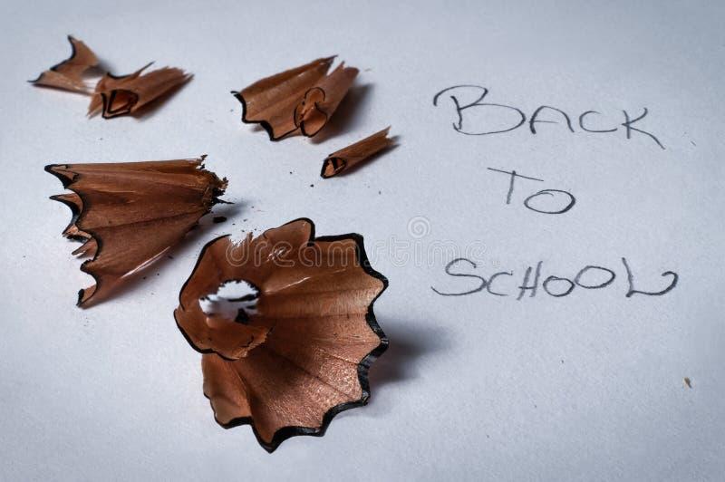 铅笔刀木漩涡削片特写镜头宏观细节在白皮书背景的与回到学校的书面文本拼写 免版税库存照片