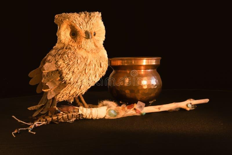 铜大锅、一支不可思议的鞭子有石英和紫色的水晶的和由自然材料做的猫头鹰在黑背景,幽灵 免版税库存照片