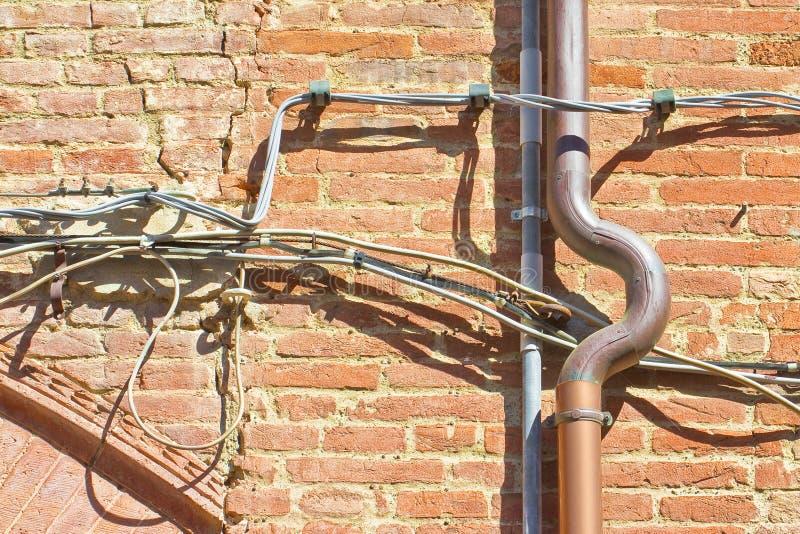 铜金管混乱扭曲的旧砖墙 免版税库存照片