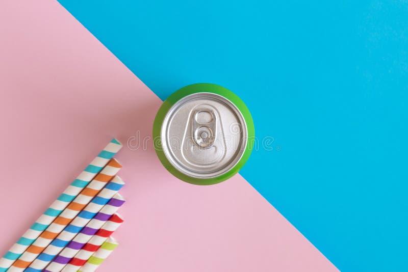 铝罐和五颜六色的吸管平的位置在淡色背景最小的夏天饮料创造性的概念 免版税库存图片