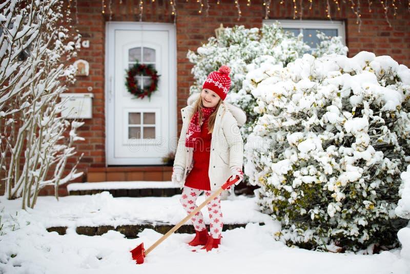 铲起冬天雪的孩子 孩子清除车道 库存照片
