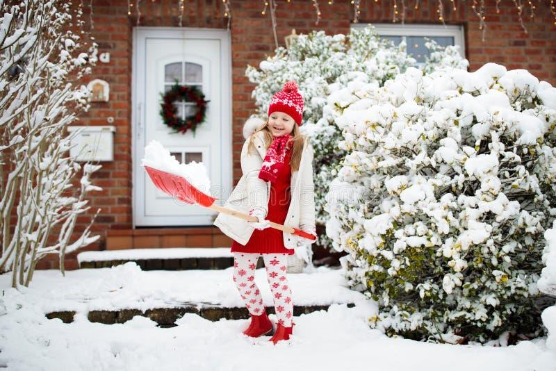 铲起冬天雪的孩子 孩子清除车道 免版税库存图片