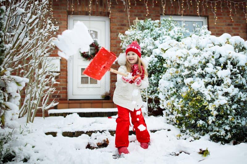 铲起冬天雪的孩子 孩子清除车道 免版税库存照片
