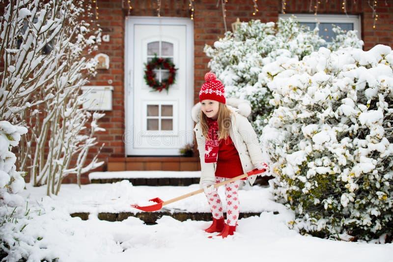 铲起冬天雪的孩子 孩子清除车道 库存图片