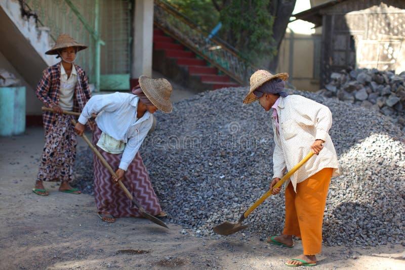 铲起沙子,妇女的妇女工作在缅甸的建筑 免版税库存照片