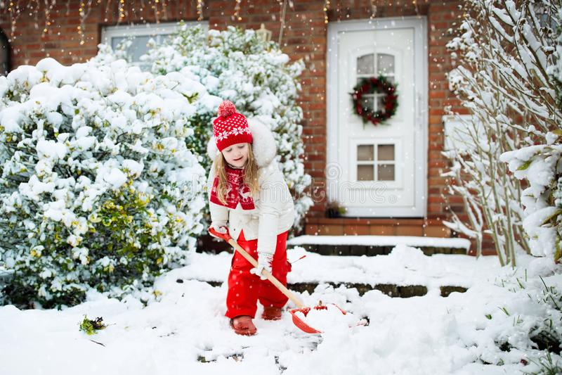 铲起雪的孩子 有锹清洁车道的小女孩在冬天暴风雪以后 以后安置门的孩子清楚的道路 库存照片