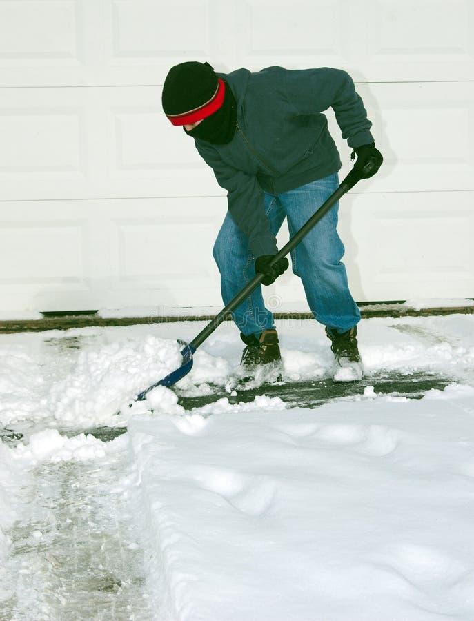 铲起雪的男孩 免版税库存照片