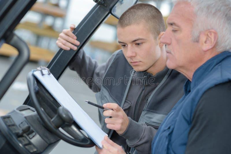 铲车司机读书剪贴板 免版税库存照片