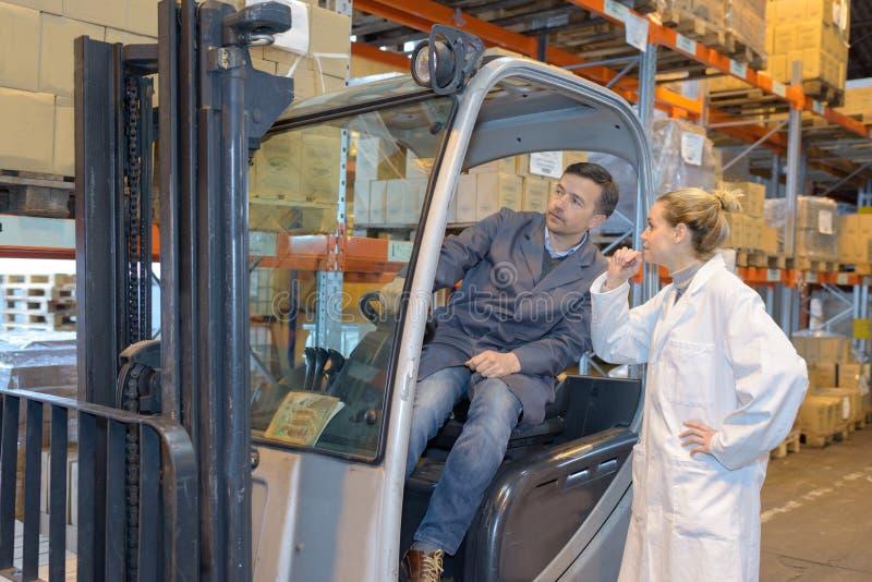 铲车的人谈话与妇女 免版税库存图片
