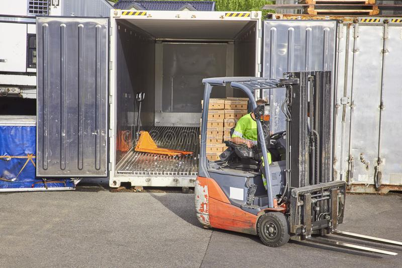 铲车装货汽车的工作者 免版税图库摄影