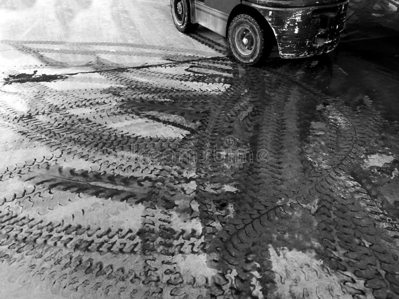 铲车轮胎轨道在肮脏的地面的在黑白摄影 库存图片