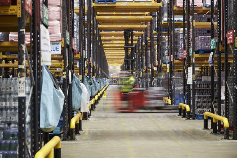 铲车驾驶横跨一个走道的在仓库里,行动迷离 免版税库存照片