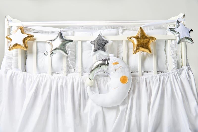 银、金子和白色星状枕头和睡觉月亮坐垫在一张白色婴儿床 免版税库存图片
