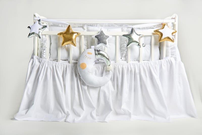 银、金子和白色星状枕头和睡觉月亮坐垫在一张白色婴儿床 免版税库存照片