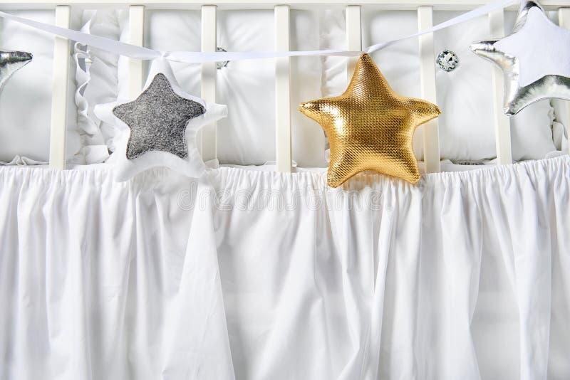 银、金子和白色星状枕头在一张白色婴儿床 图库摄影