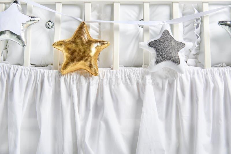 银、金子和白色星状枕头在一张白色婴儿床 免版税图库摄影