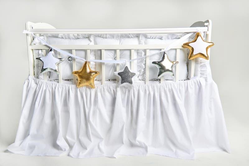 银、金子和白色星状枕头在一张白色婴儿床 免版税库存图片