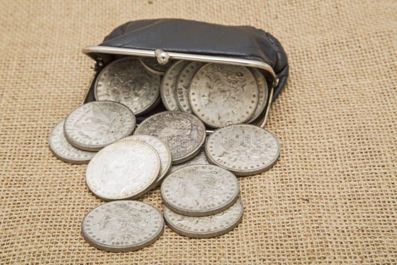 银元溢出的硬币钱包背景 免版税库存照片