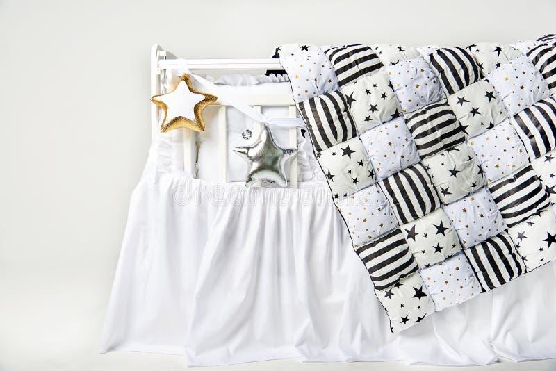 银和金星状枕头和补缀品橡皮奶嘴在一张白色婴儿床 库存图片