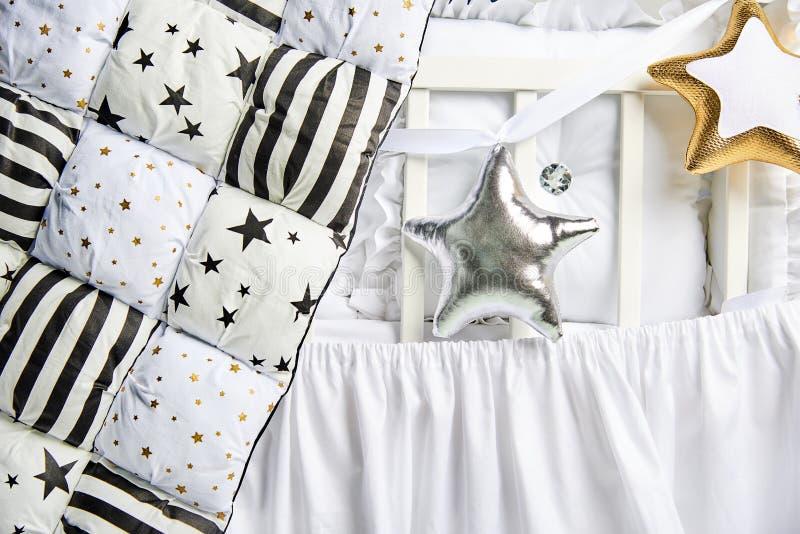 银和金星状枕头和补缀品橡皮奶嘴在一张白色婴儿床 免版税库存照片