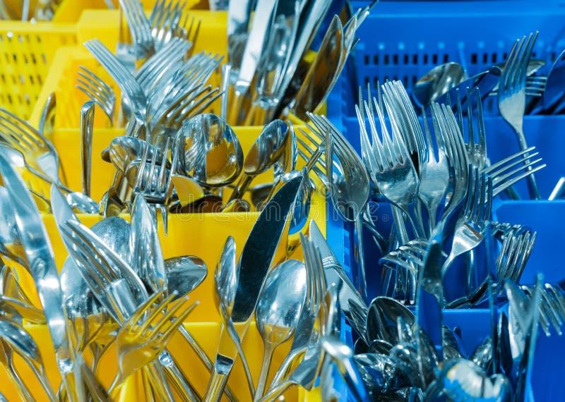 银器和利器在五颜六色的palstic ocntainer在一个工业餐馆厨房里 免版税库存照片