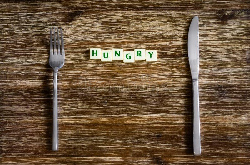 银器在与标志的木桌上设置了饥饿 免版税库存图片