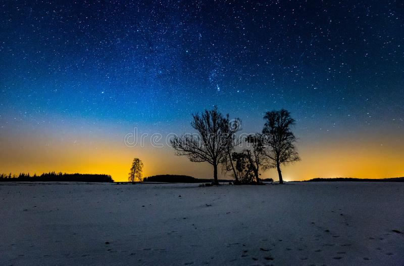 银河和满天星斗的天空在冬天风景和遥远的村庄 免版税图库摄影