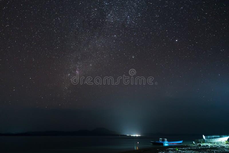银河满天星斗的天空发光的星在Gunung Api火山岛的夜弄脏了小船热带海滩印度尼西亚Banda 免版税库存照片