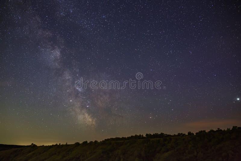 银河的星在夜空的在一个多小山风景 免版税库存图片