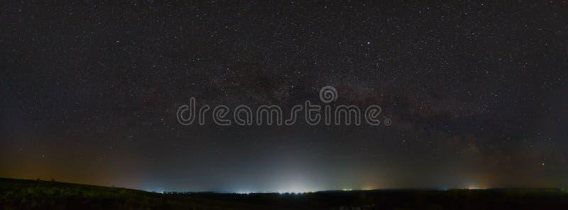 银河的星在夜空的 从街灯的光害在天际上 免版税库存图片
