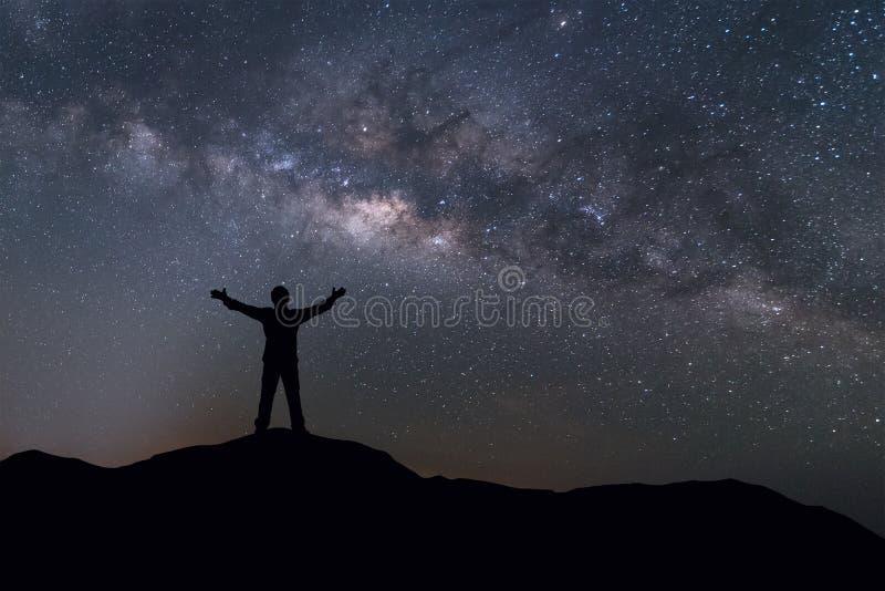银河风景 站立在与夜空和明亮的星的山顶部的愉快的人剪影在背景 免版税库存照片