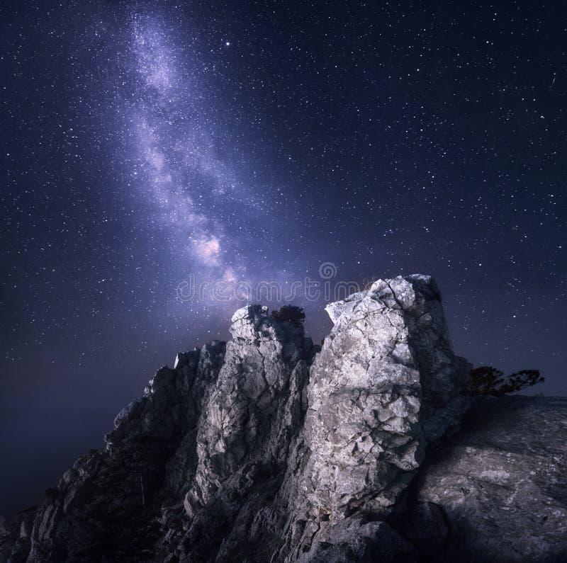 银河 与岩石和满天星斗的天空的美好的夜风景 免版税图库摄影