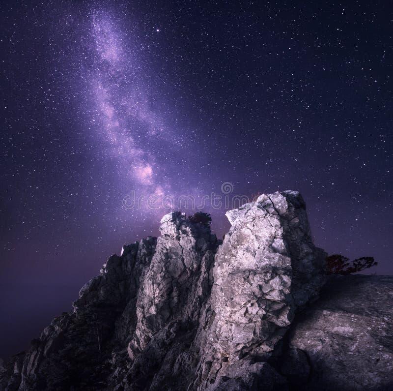 银河 与岩石和满天星斗的天空的美好的夜风景 免版税库存照片