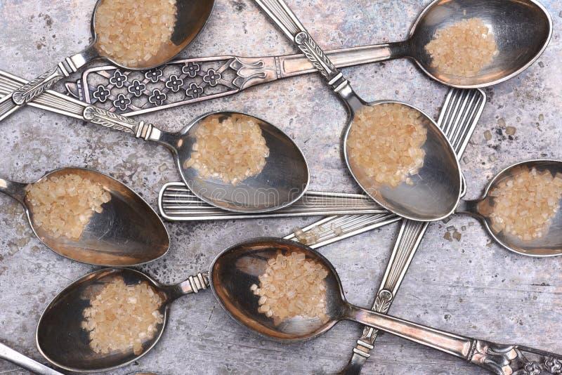 银色一匙用在金属桌上的红糖 免版税库存图片